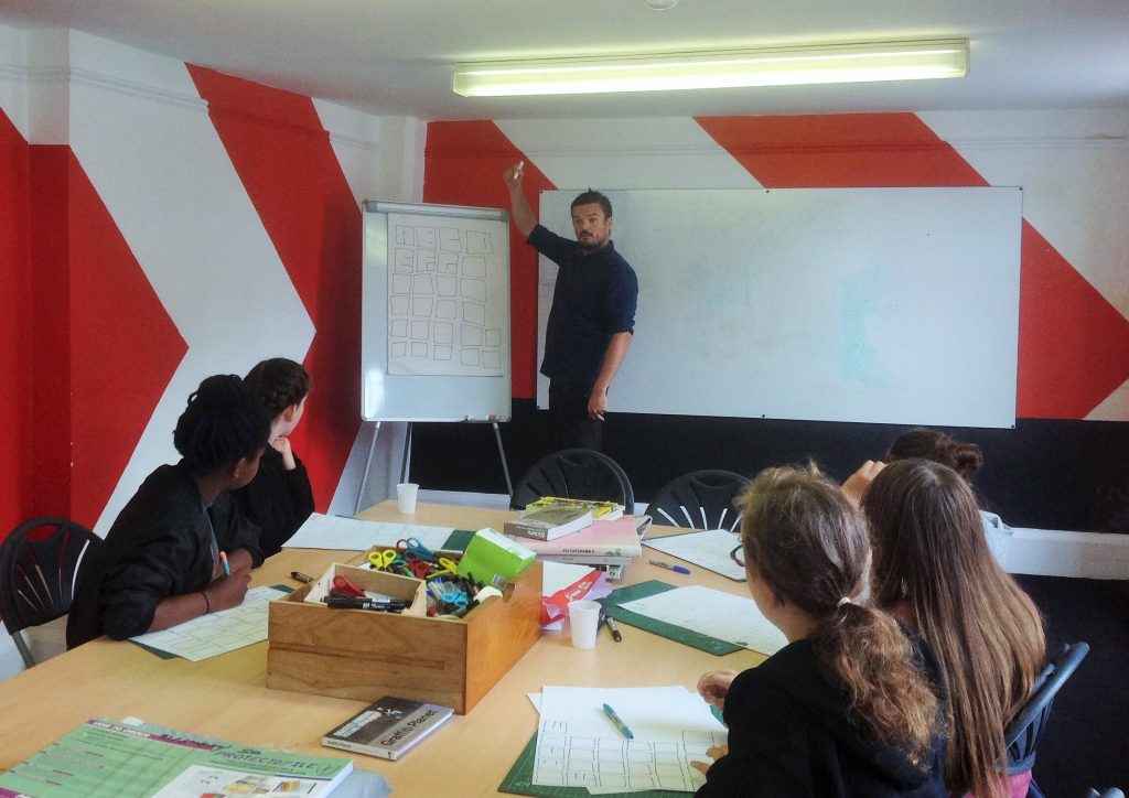 Artist explains graffiti letters on flipchart