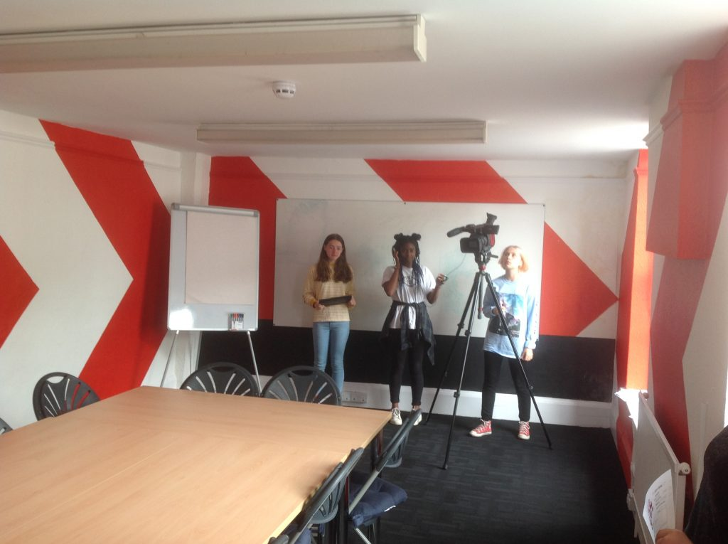 Young people learning to use filming equipment