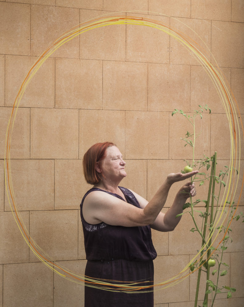 A photo of a woman behind a window. She is holding a tomato growing on a plant.