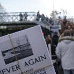 In focus shot of A5 postcards titled Never Again. In the background a crowd watching singers perform on a bridge