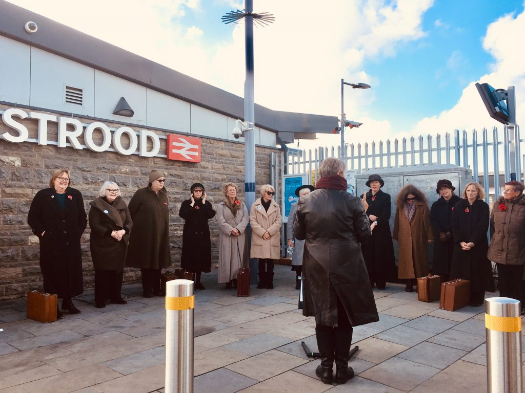 Singers standing side by side at Strood station