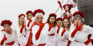 A group of female performers dressed in white outfits with red gloves and capes.