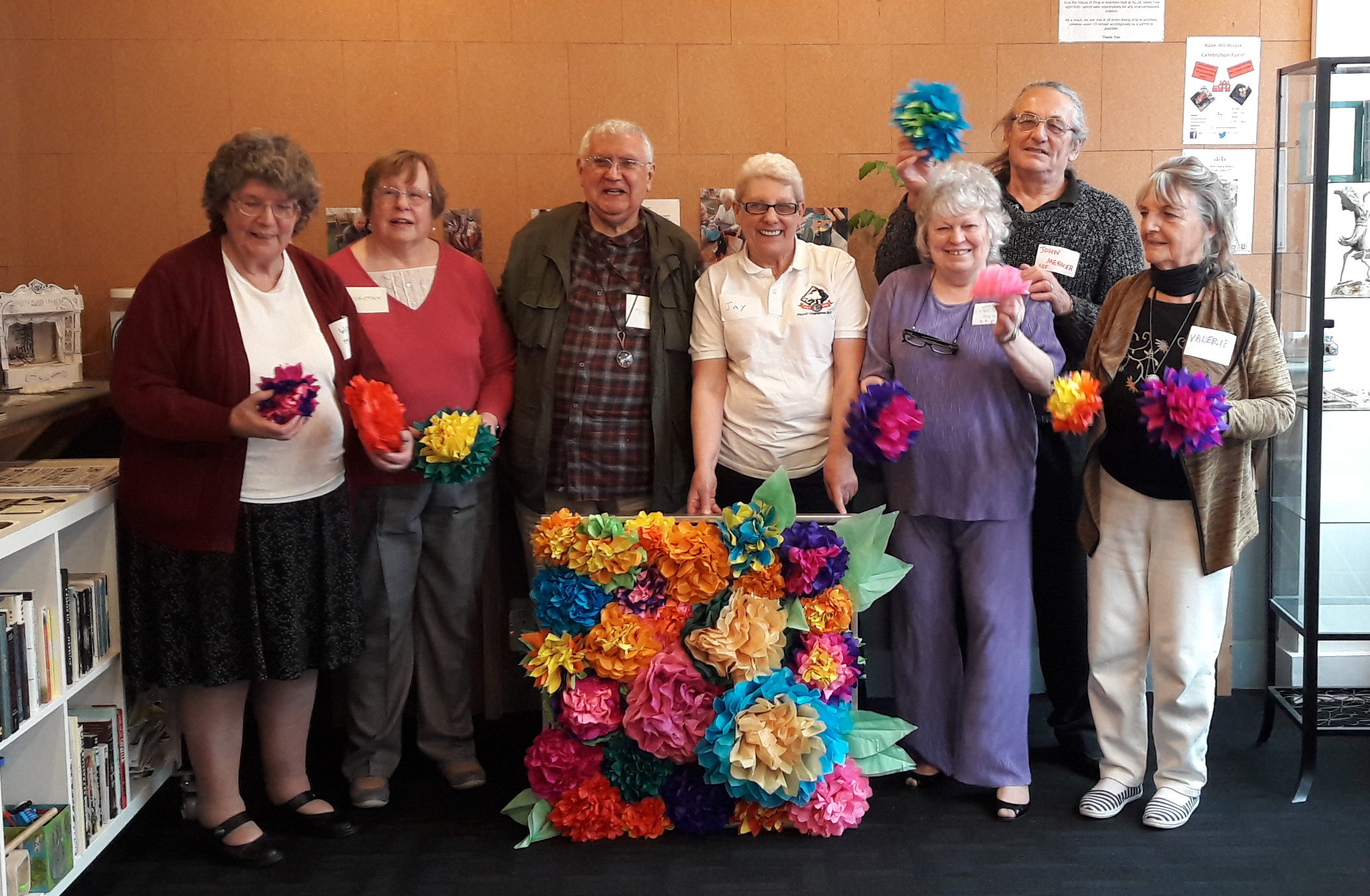 A group of over 55s with their craft creation of a floral paper canvas.