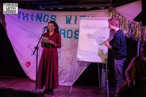 Neelam performing on stage with her husband, Adrian. Neelam is standing in front of a microphone. Adrian is in front of a flipchart board that he has been drawing on.