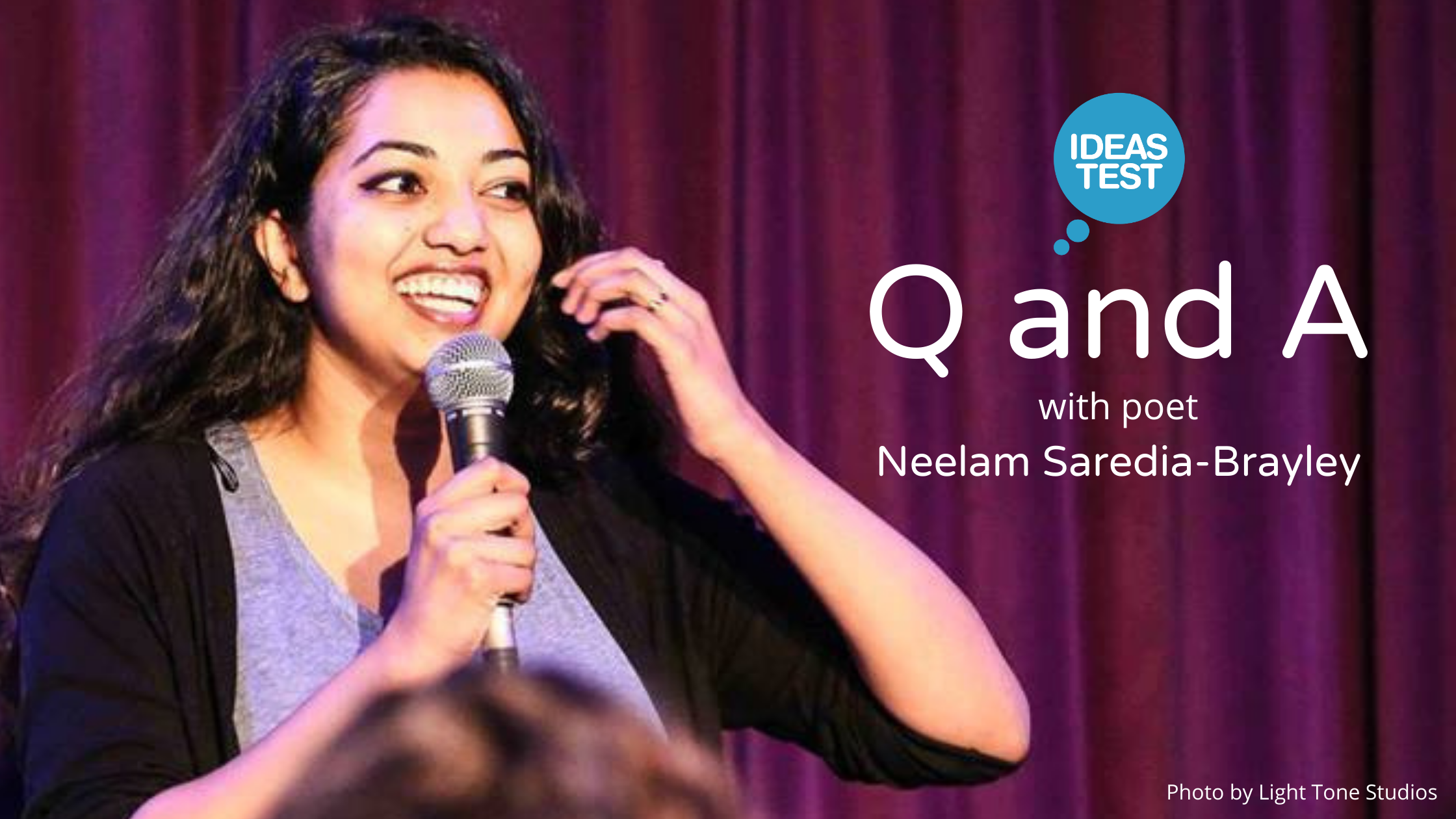 Photo of poet Neelam Saredia-Brayley. Neelam is a young woman who is standing in front of a stage curtain in front of an audience. She is holding a microphone and smiling.