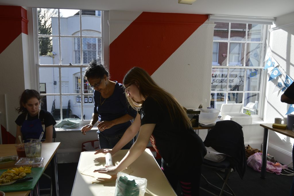 Young person rolling out dough