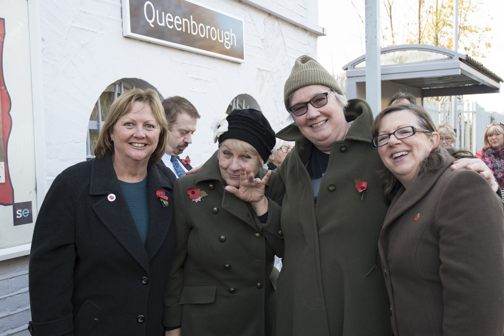 Four choir members smiling at a train station