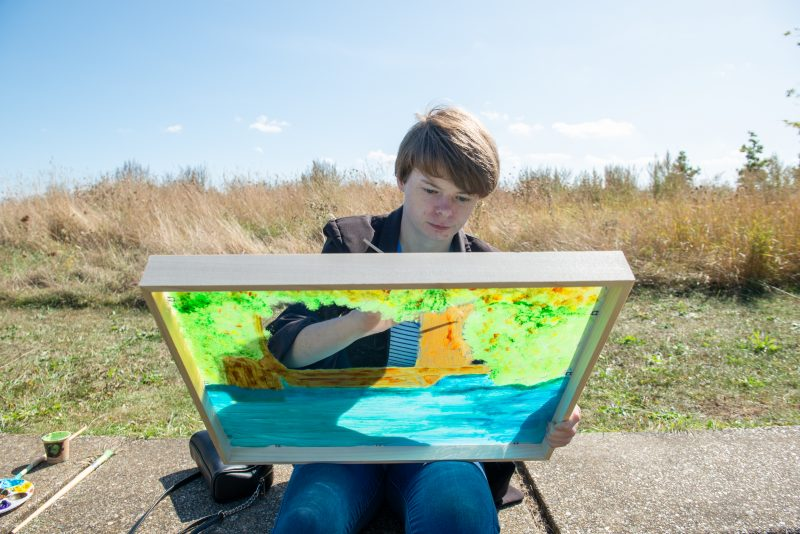Shannon Cole painting on an clear acrylic sheet in Milton Creek Country Park