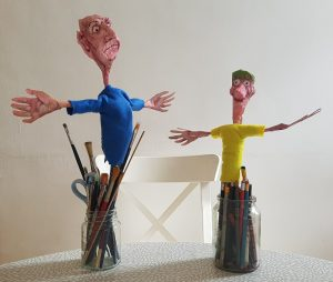 A photo of two handmade puppets. They have their arms outstretched. The puppets are propped up in jars containing pencils and paintbrushes.