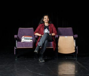Neelam is a young woman sitting on a black stage. There are three chairs on the stage. Neelam is sitting in the centre chair. The other chairs have books on them.
