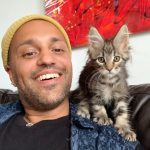 Anil is a smiling person who is wearing a yellow beanie hat and a blue shirt with a black top underneath. They are sitting on a black sofa and have a red artwork behind them. On Anil's shoulder is a very fluffy grey tabby cat who is looking at the camera.