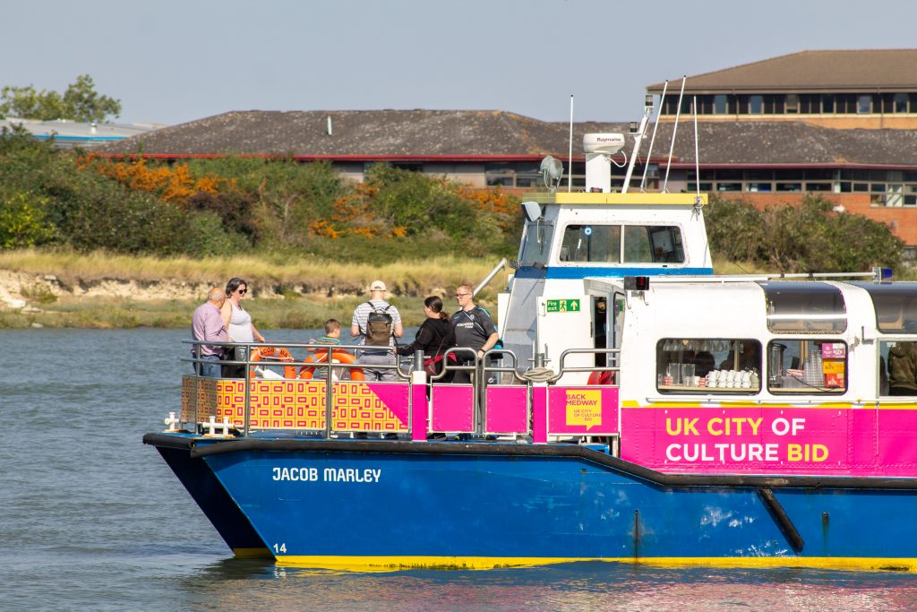 A blue and white boat with passengers on it. It is moving right to left. It is decorated in pink and orange Medway 2025 logos.