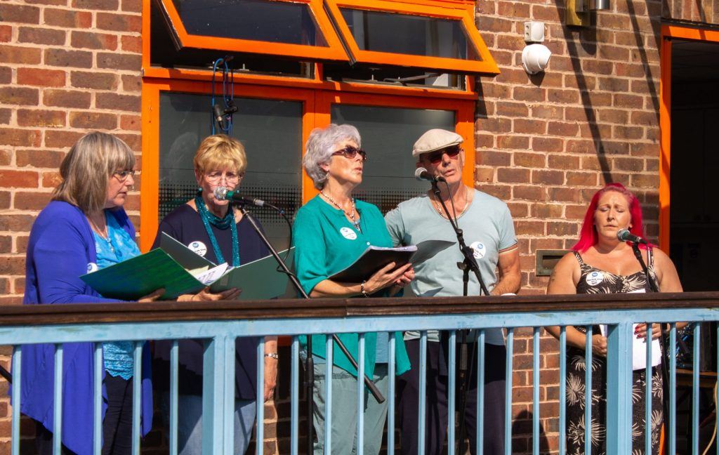 A group of five people singing on a balcony.